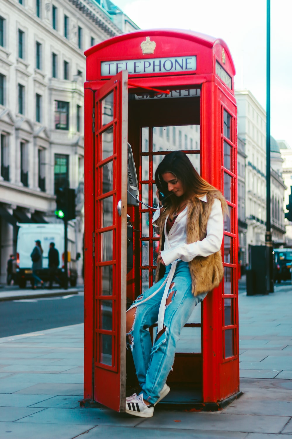woman in white jacket and blue denim jeans standing on red telephone booth