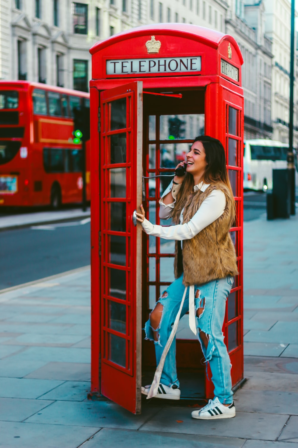 woman in brown long sleeve shirt and blue denim jeans leaning on red telephone booth