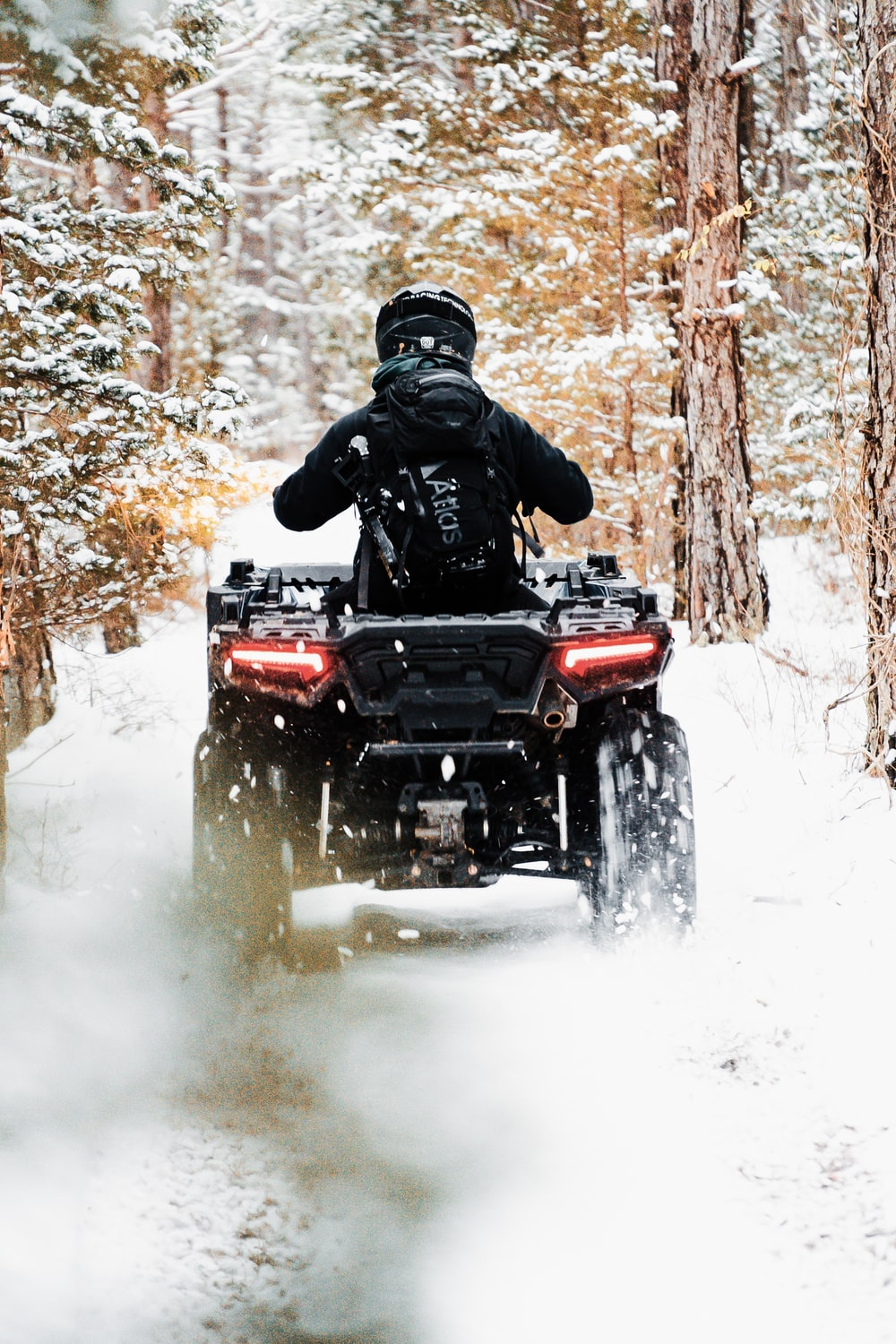 man riding red atv on snow covered ground during daytime