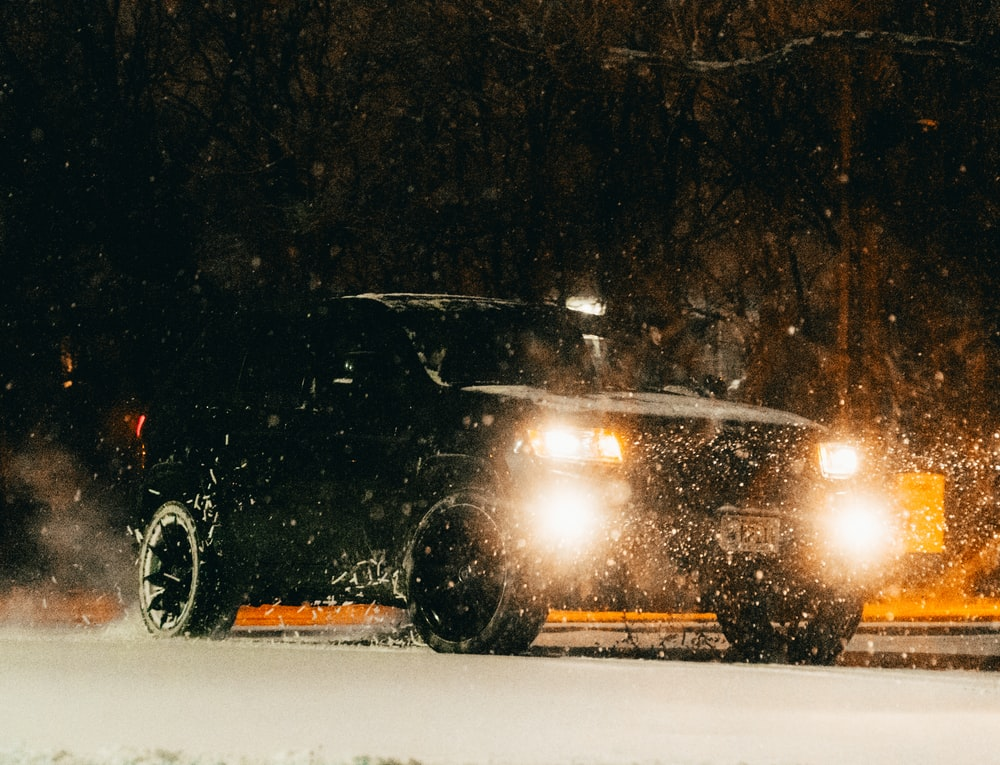 black car on snow covered road during night time