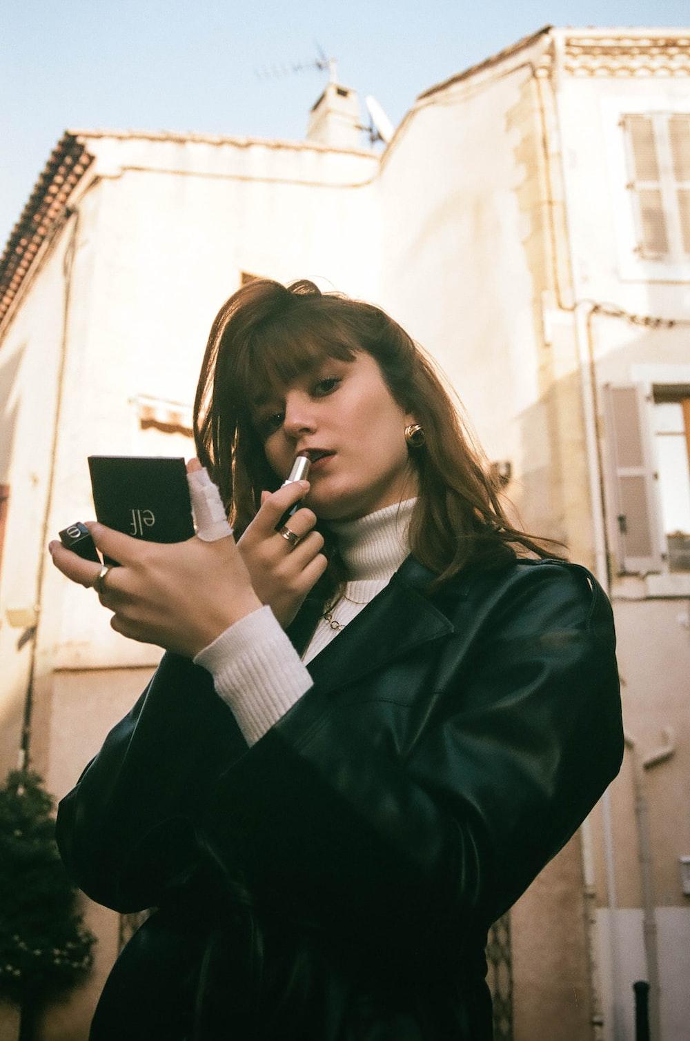 woman in black blazer holding black smartphone