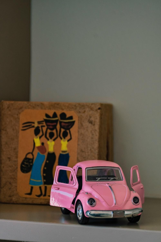 pink car toy beside brown cardboard box