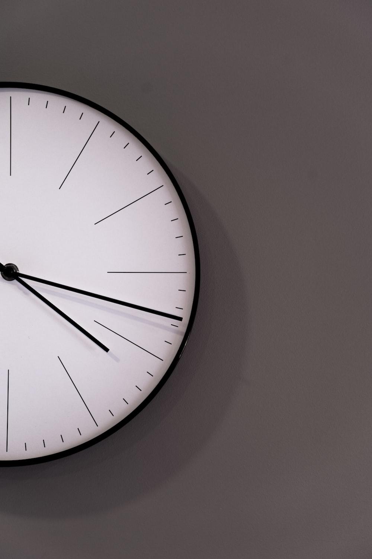 white analog wall clock at 11 00