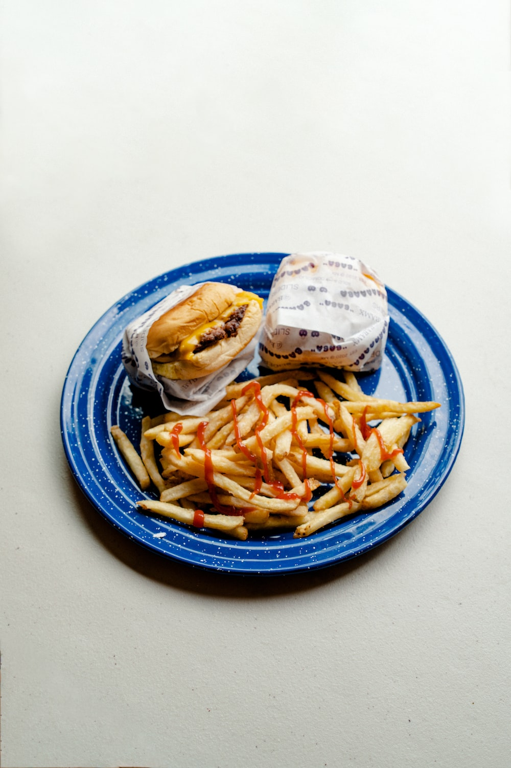 burger and fries on blue and white ceramic plate