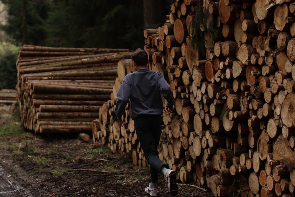 man in black jacket and black pants standing on wood logs