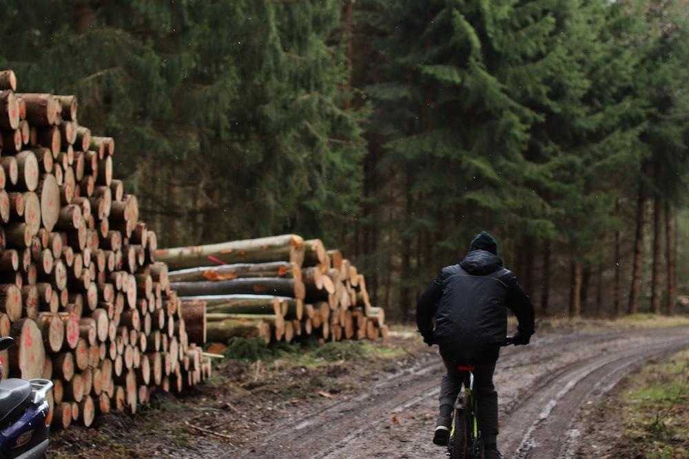 man in black jacket walking on road during daytime