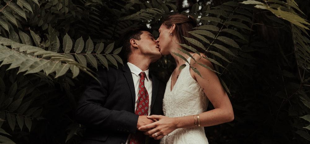 man in black suit kissing woman in white wedding dress