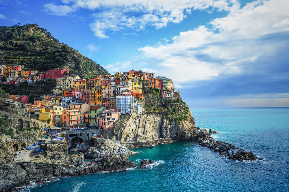 houses on mountain beside sea under blue sky during daytime
