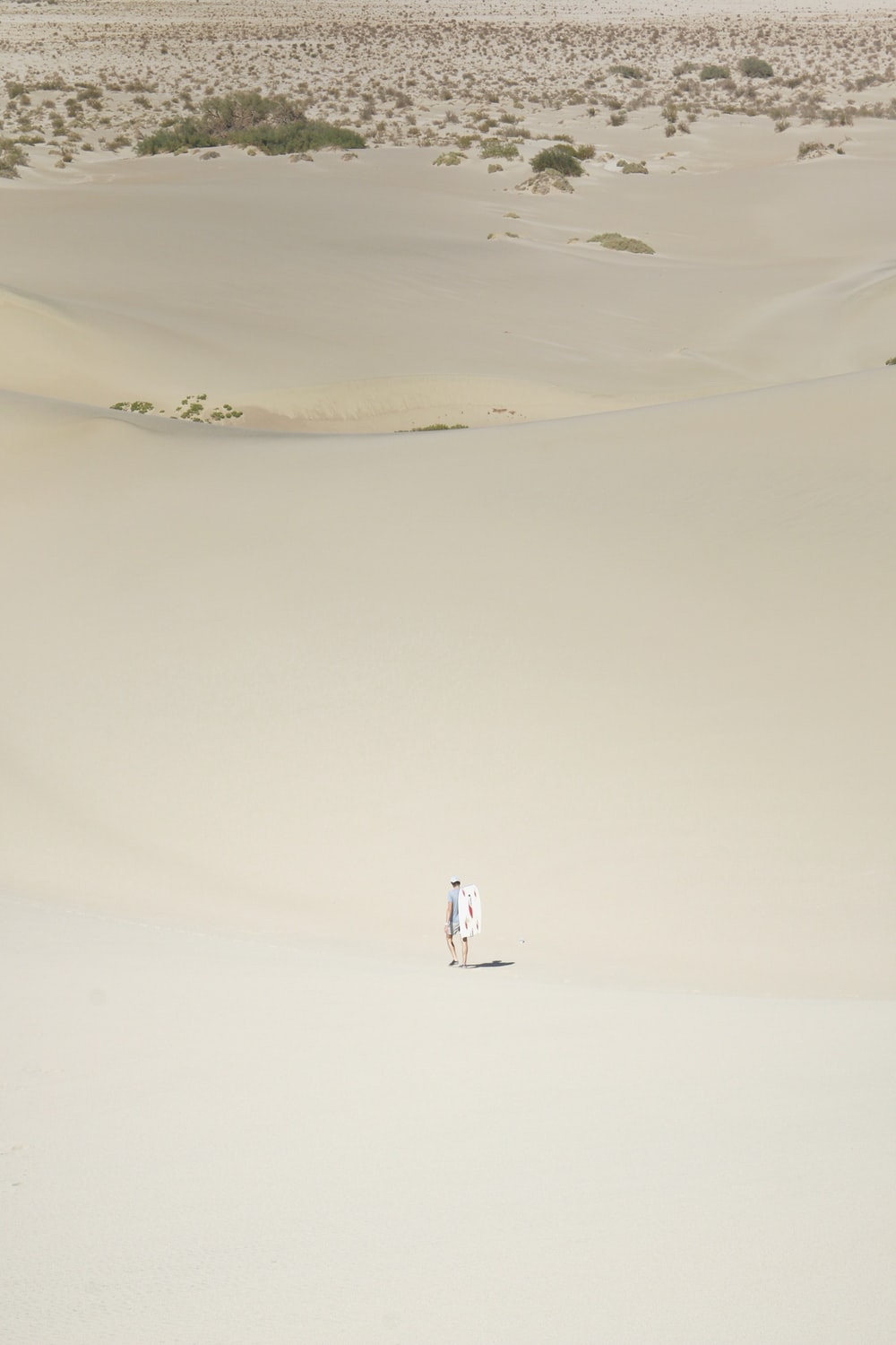 person in white shirt walking on sand