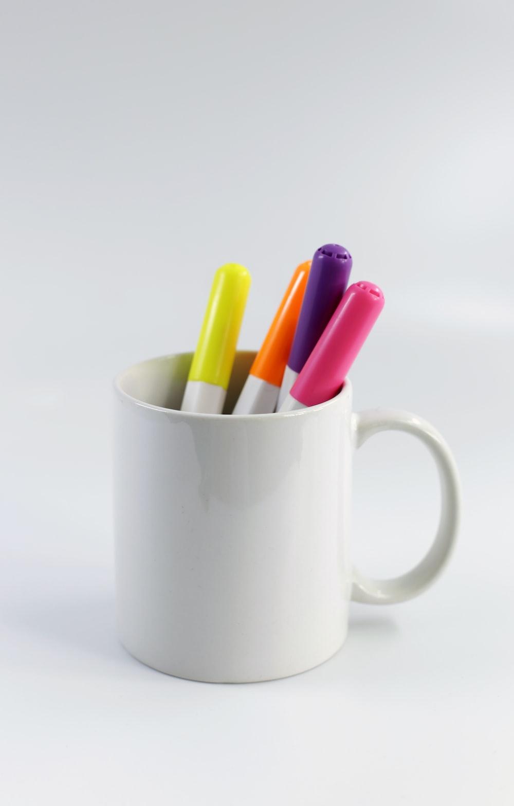 white ceramic mug with assorted color pencils