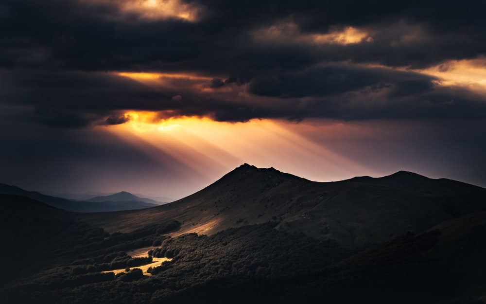 black and white mountain under cloudy sky during sunset