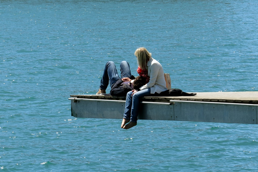 3 women sitting on concrete bench near body of water during daytime