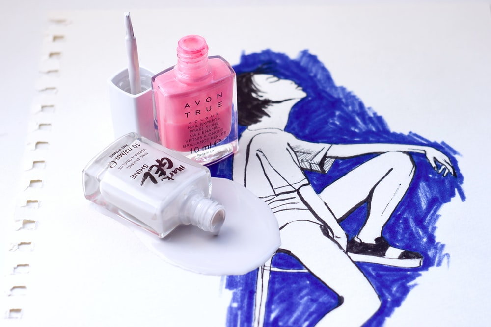 pink nail polish bottle on white and blue textile