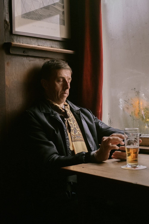 man in black jacket sitting beside brown wooden table