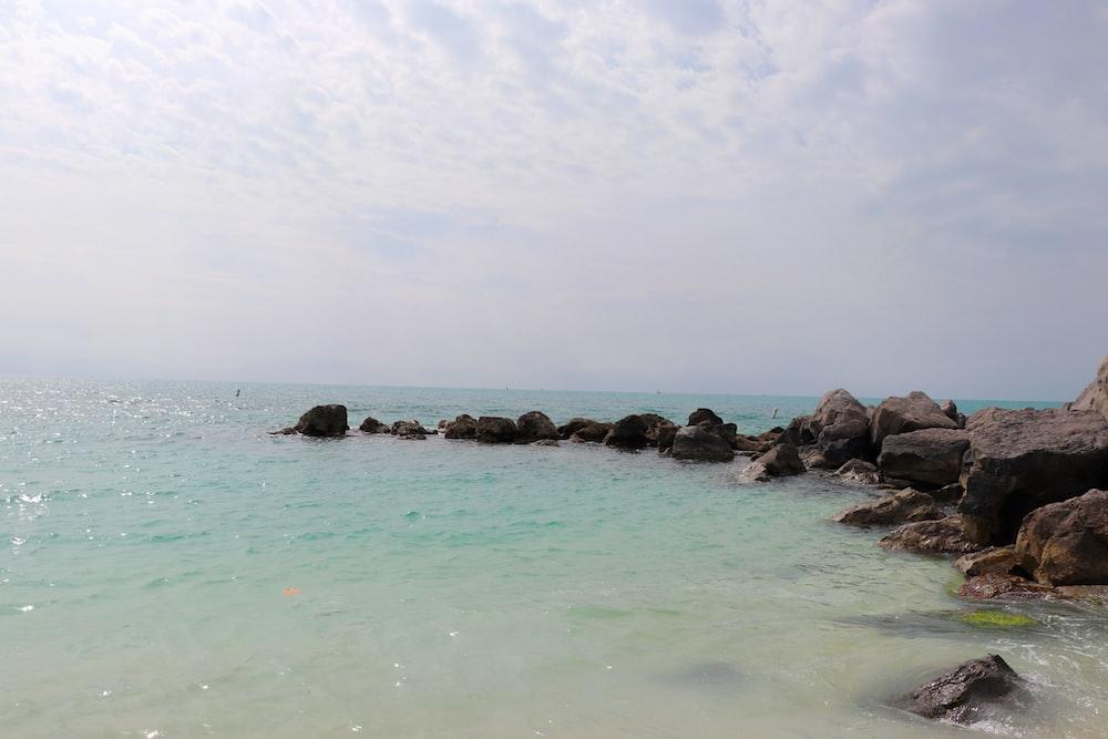 gray rocks on sea under white sky during daytime