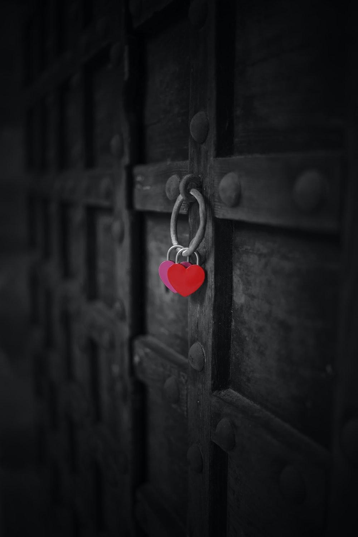 red heart padlock on brown wooden door