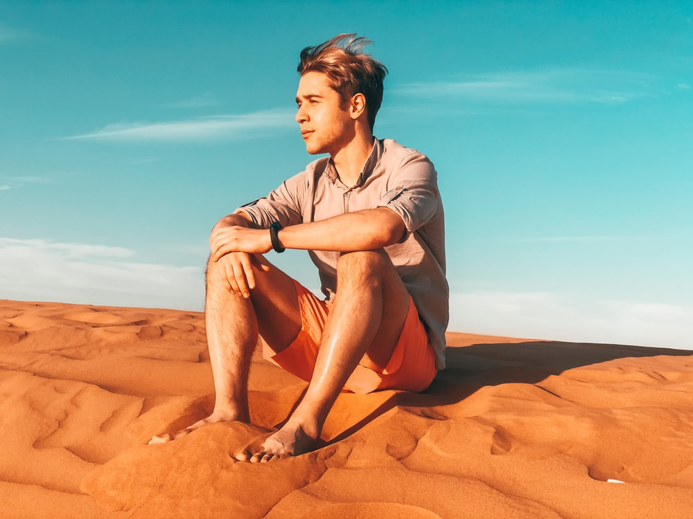 man in grey button up shirt sitting on brown sand during daytime