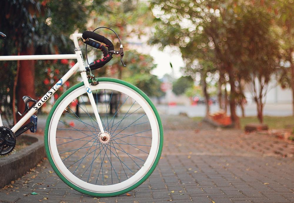 white and black city bike on brown brick floor during daytime