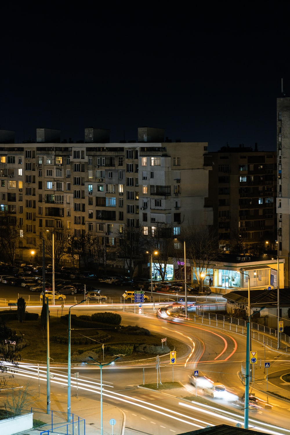 time lapse photography of cars on road near high rise building during night time