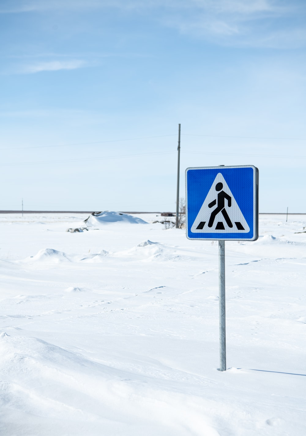 blue and white no smoking sign on snow covered ground