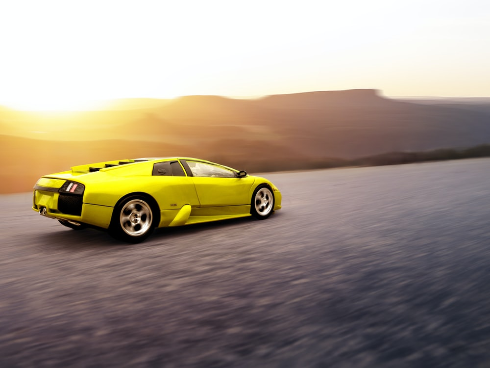 yellow coupe on gray sand during daytime