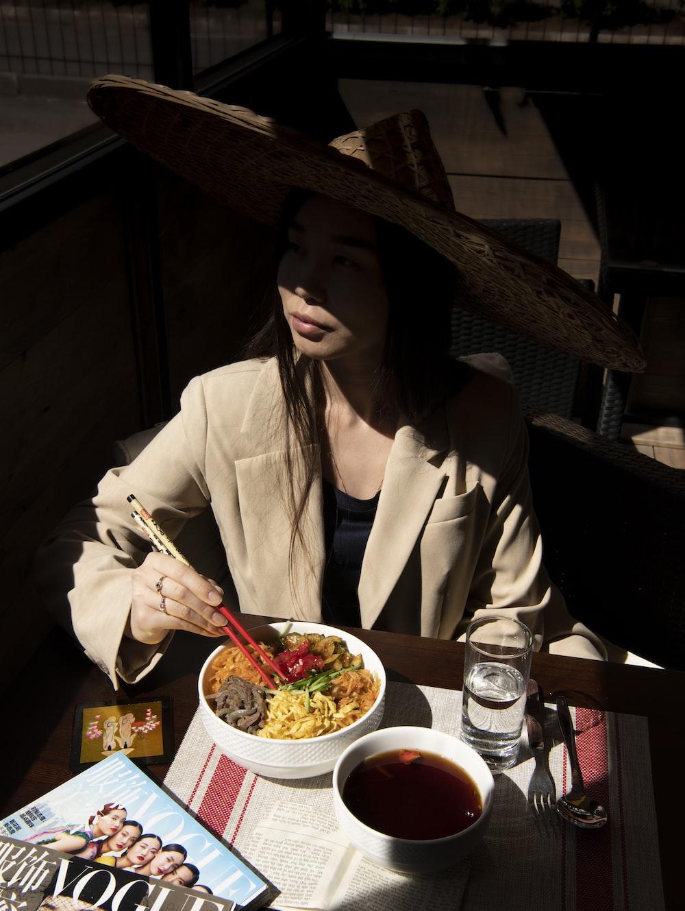 woman in white blazer holding chopsticks