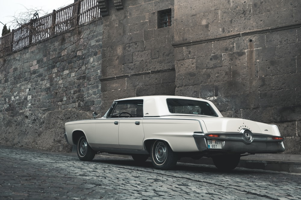 white classic car parked beside brown brick wall