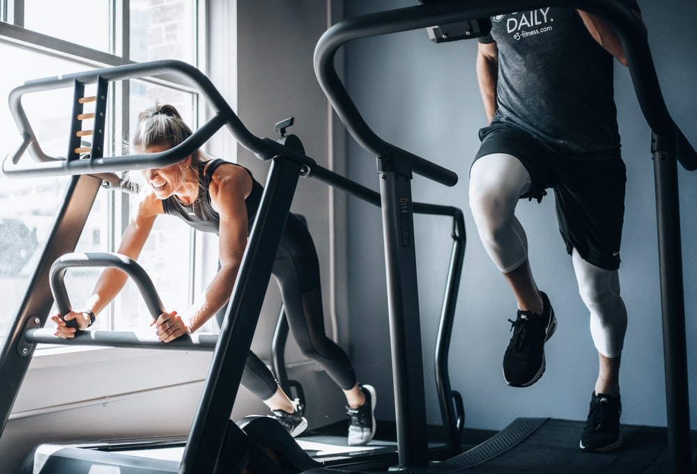 woman in black tank top and black shorts sitting on black exercise equipment