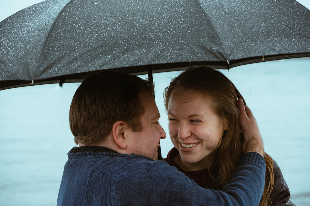 man and woman under black umbrella during daytime