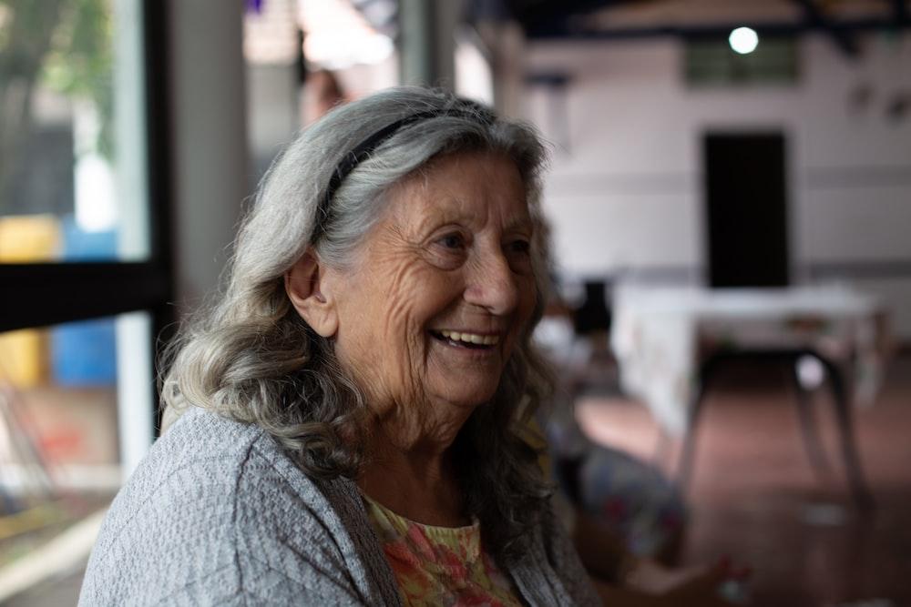 smiling woman in gray cardigan