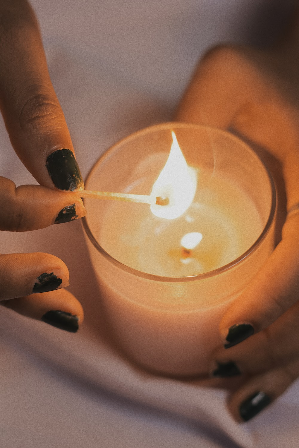 person holding lighted candle stick