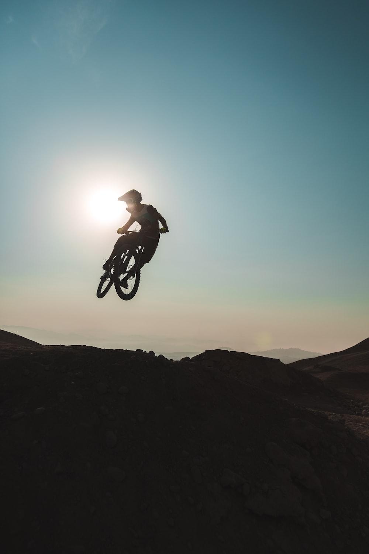 man riding on bicycle on mountain during daytime