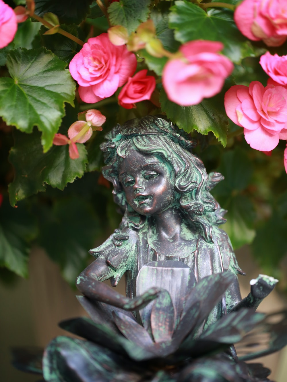 woman with pink rose on her head statue