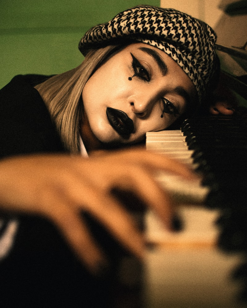 Woman in sad clown makeup leaning on a piano keyboard with hands on keys.