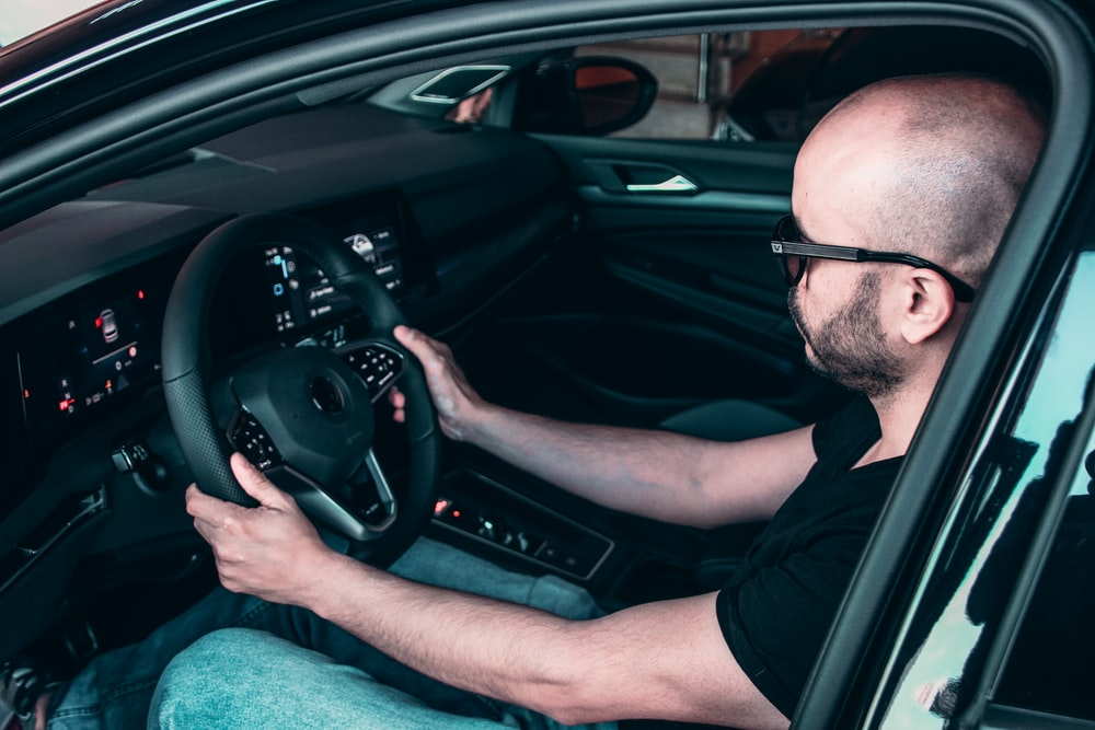 man in black framed eyeglasses driving car