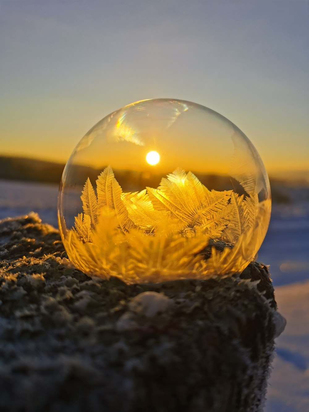clear glass ball on black and gray rock