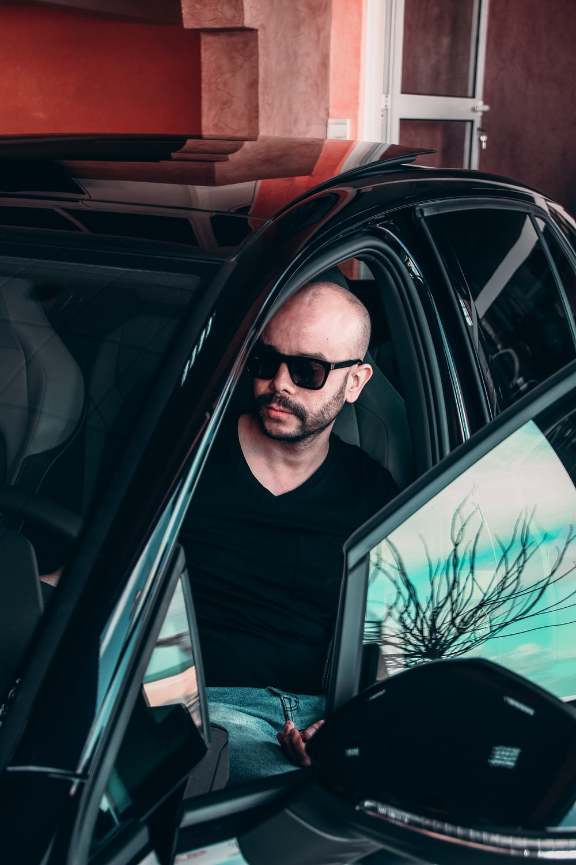 man in black v neck shirt wearing black sunglasses inside car