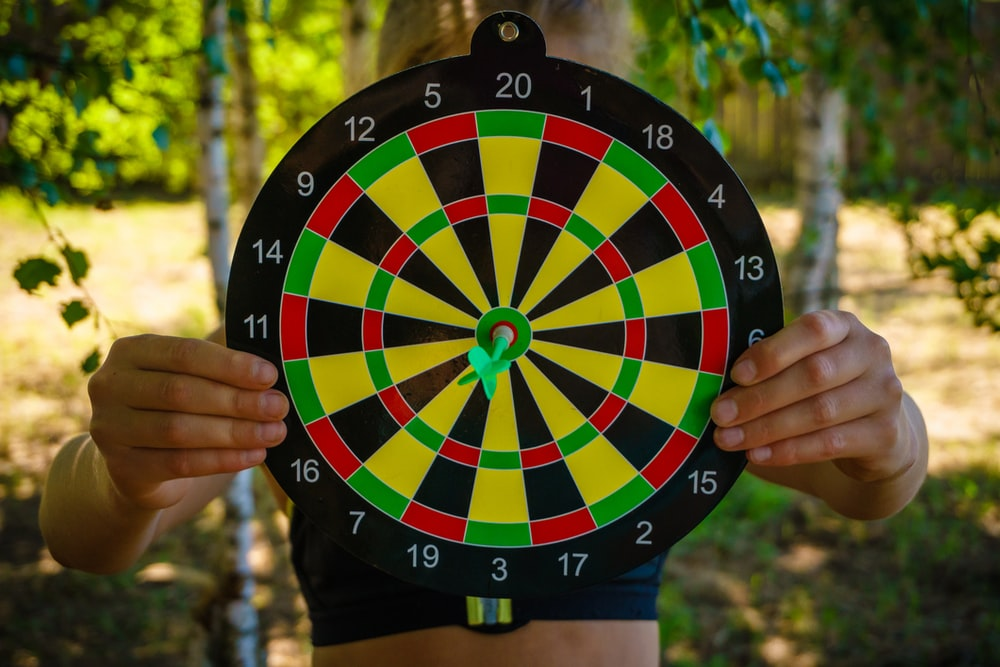 person holding black red yellow and green round analog clock