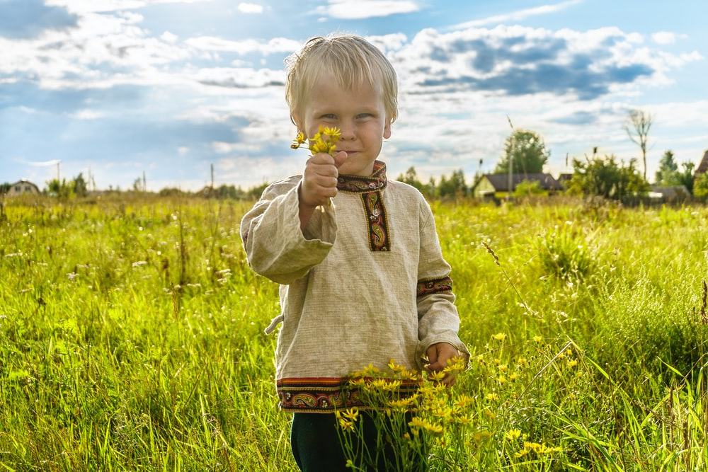 boy in gray sweater standing on green grass field during daytime