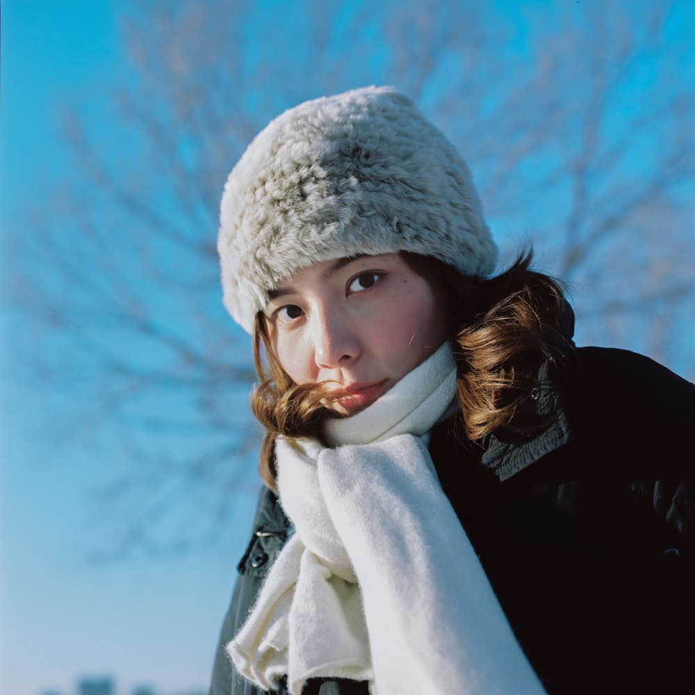 woman in white winter coat and gray knit cap