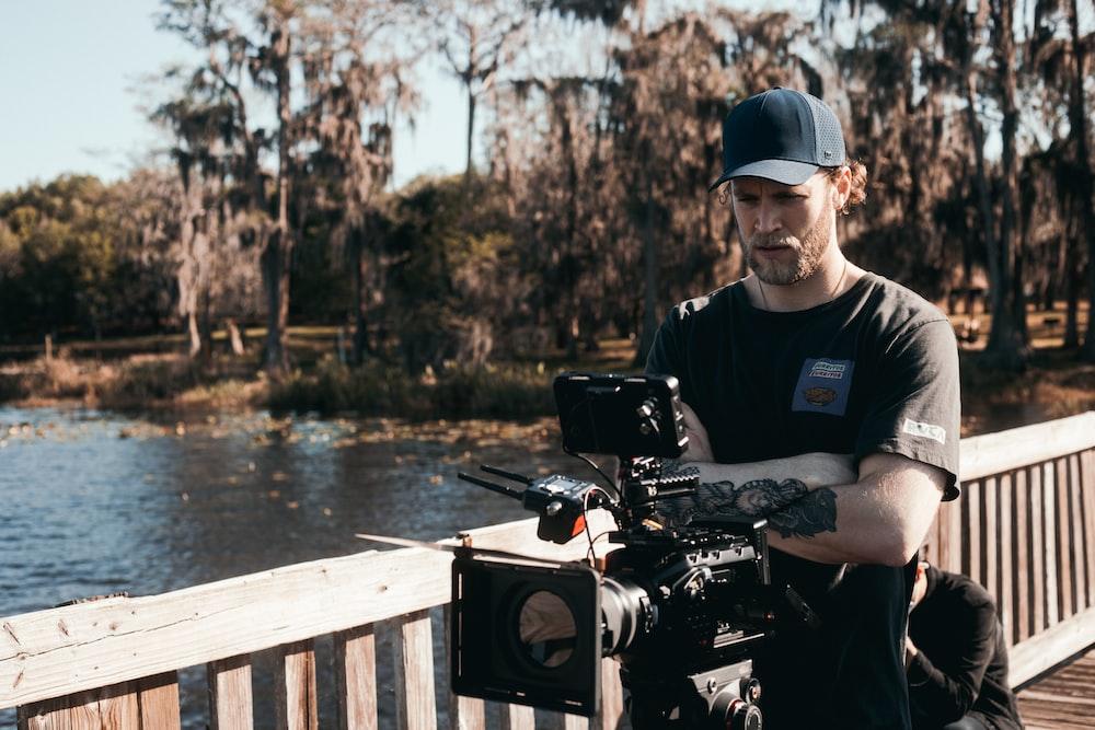 man in black polo shirt and blue cap holding black dslr camera