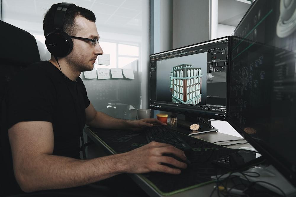 man in black tank top wearing black sunglasses using computer
