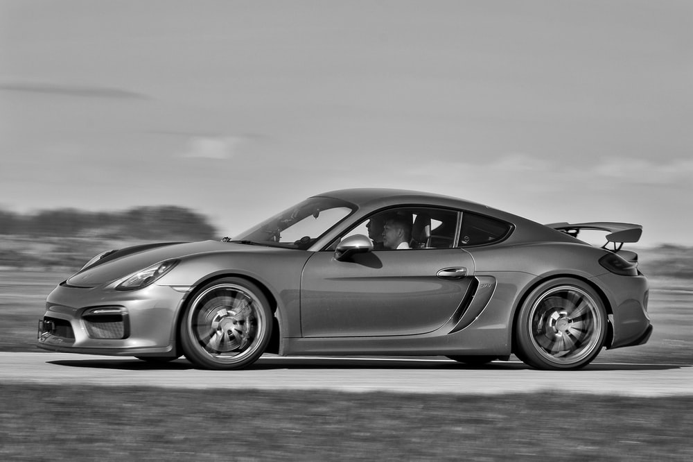 grayscale photo of coupe on road