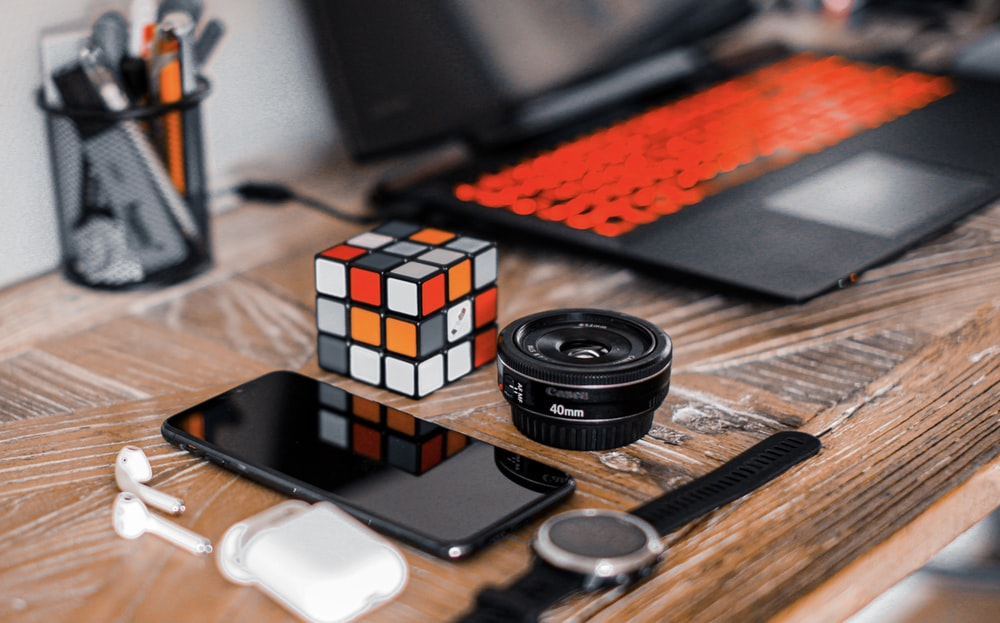 black dslr camera lens beside black camera lens and silver iphone 6 on brown wooden table