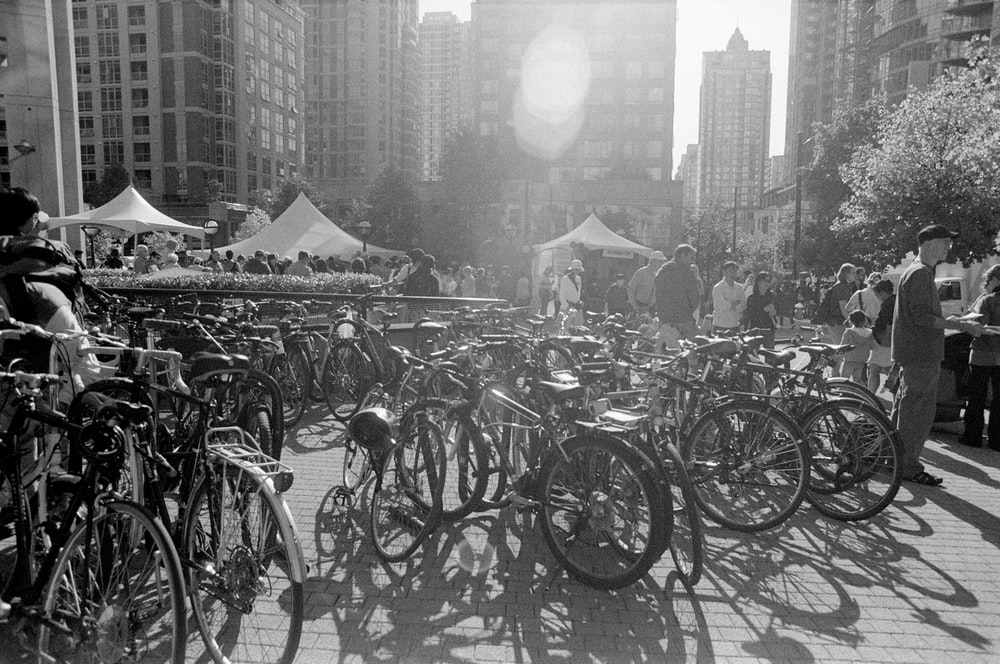 grayscale photo of bicycles parked on the side of the road