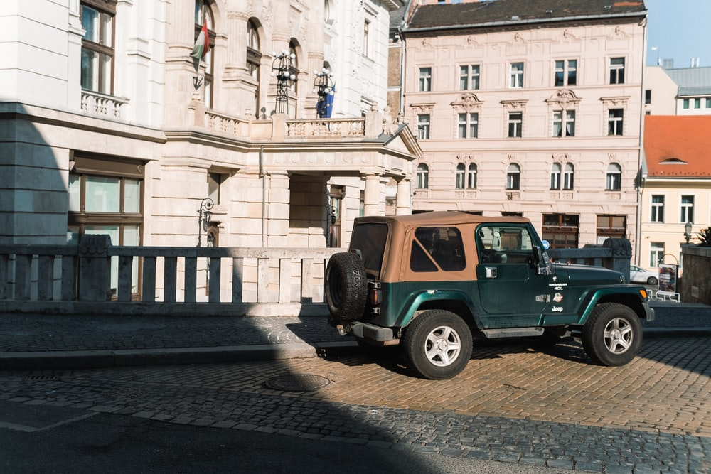 green suv parked beside beige concrete building during daytime