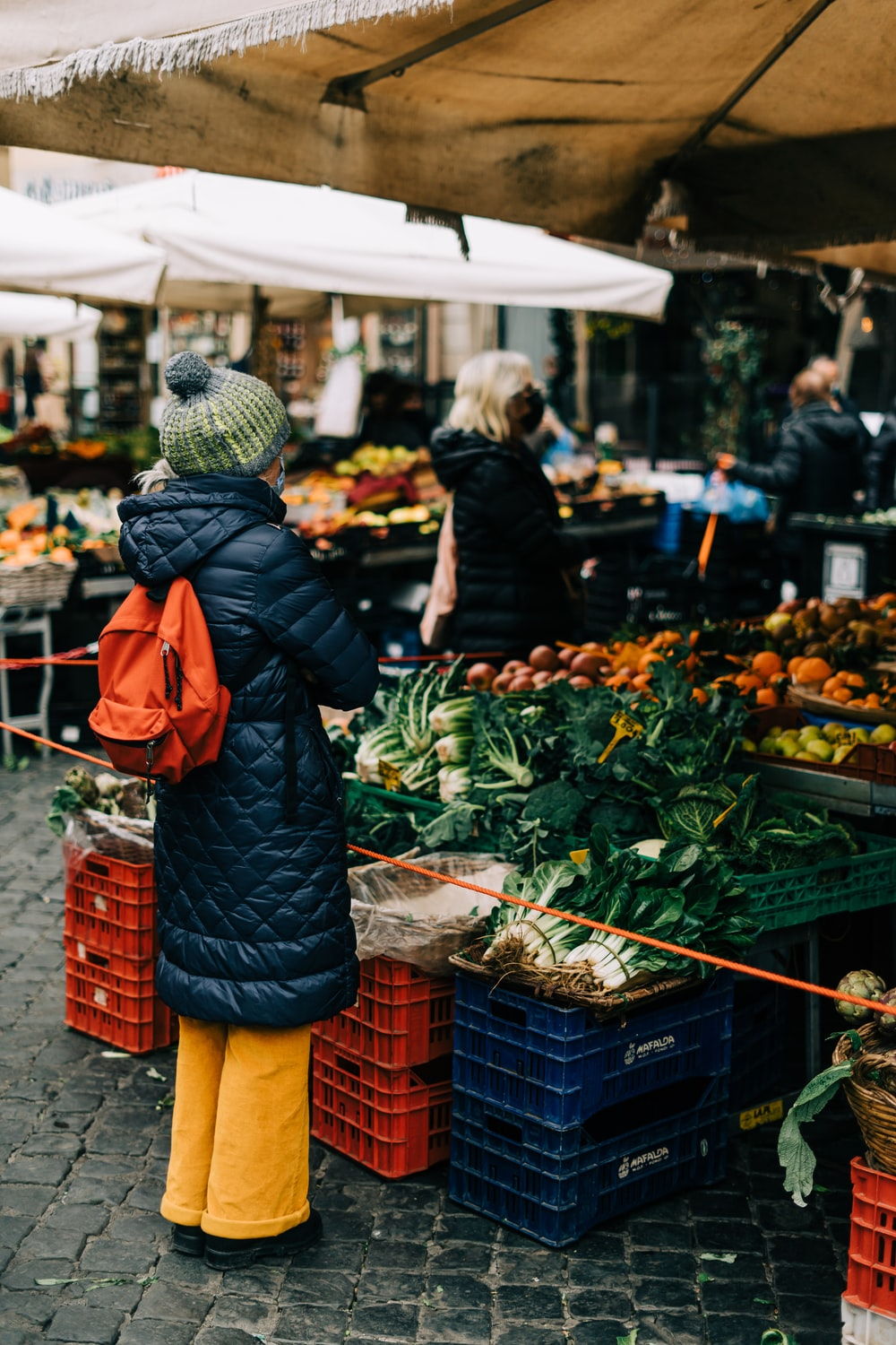 woman in black knit cap and orange coat standing in front of green vegetable display