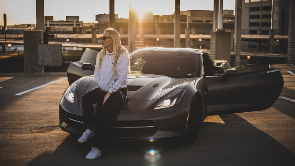 woman in white long sleeve shirt and black pants sitting on black car