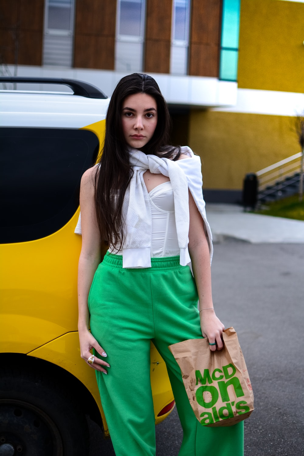 woman in white shirt and green shorts standing beside yellow car
