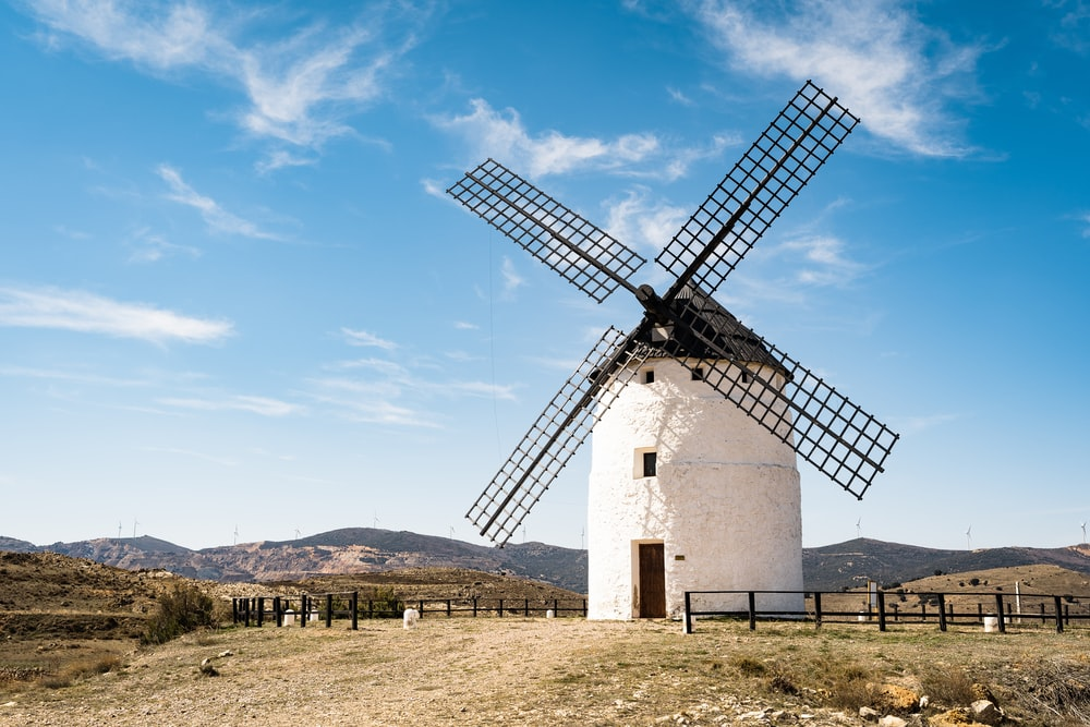 white and brown windmill under blue sky during daytime